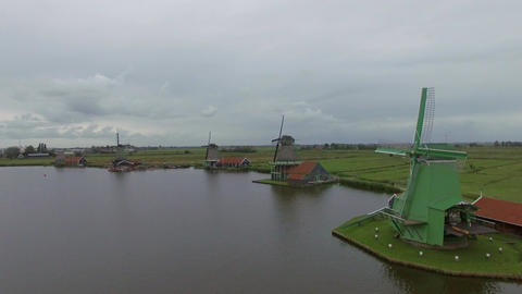 Riverside windmills and green field, aerial view Footage