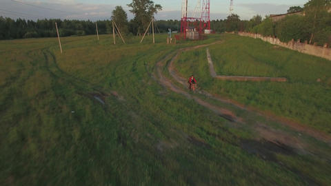 Teenager riding bike in the country, aerial view Footage