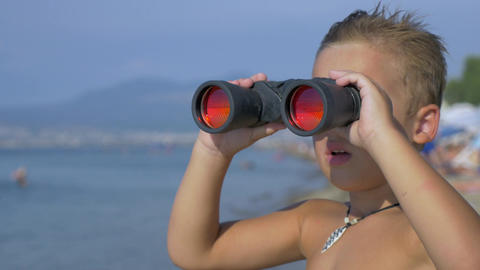 Child exploring the sea with binoculars Footage