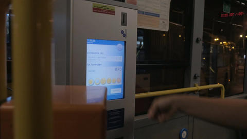 Woman using ticket machine to pay for bus ride Footage