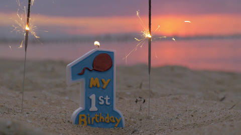 One year old baby boy birthday candle on the beach Footage