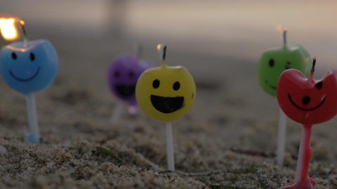 Colorful smiley candles on the beach ビデオ