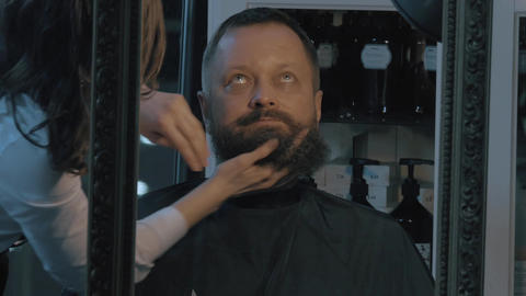 Close up view of female barber taking cares of lush beard of man. Barber applyin Live Action
