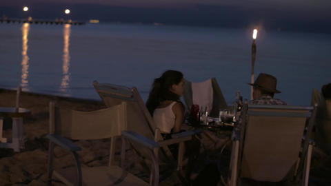 View of young happy couple having romantic dinner on the beach, Greece ビデオ