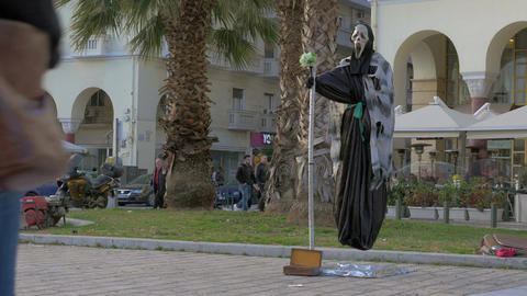 In sunny day a street performer in costume of death shows a trick how to fly in  Footage