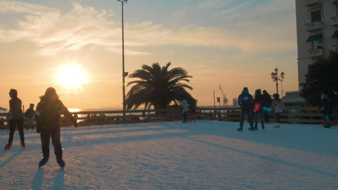 People skating on ice-rink at sunset, Greece Filmmaterial
