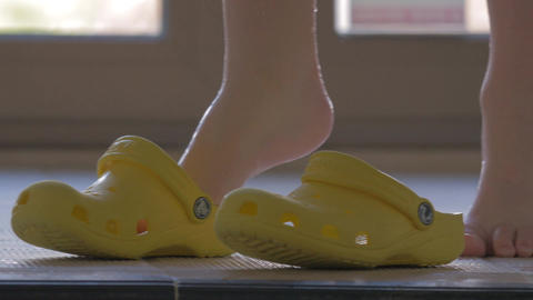 Child putting on rubber shoes after swimming in pool Live Action