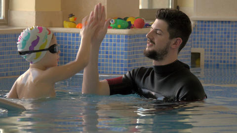 Rehabilitation Centre Evexia, swimming lesson, small boy and teacher in swimming Footage