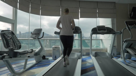 Woman training on treadmill and enjoying cityscape Live Action