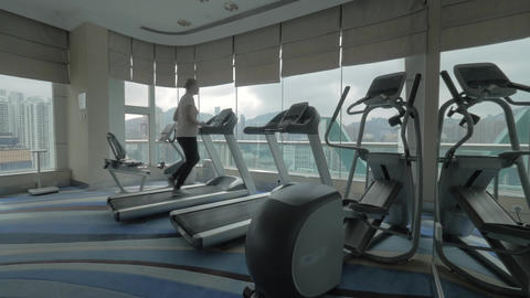 Woman working out on running machine and looking at city Footage