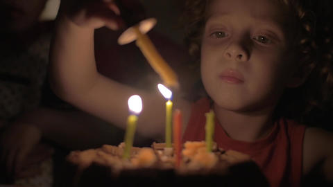 Slow motion view of small girl lighting the candles on birthday cake in the dark Footage