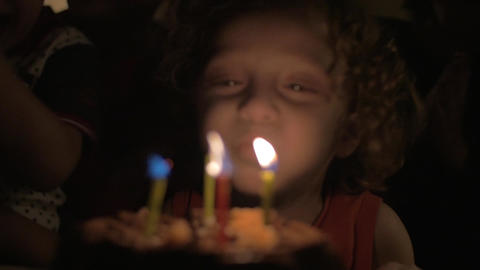 Child blowing candles on birthday cake Footage