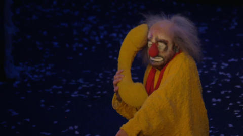 On snow show of Slava Polunin acts clown in a yellow suit and talking on a toy t Footage