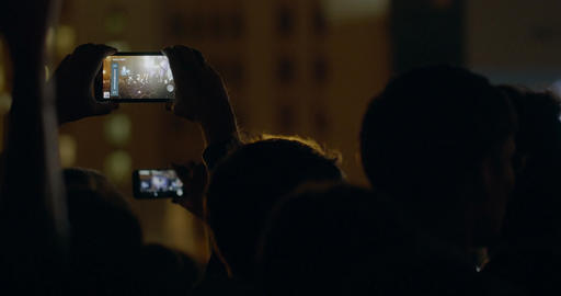 Spectator man recording video with zoom of stage and big screen via smartphone a Footage