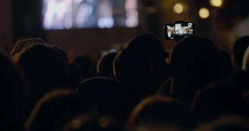 View from behind of hands hold camera with digital display among people at rave  Footage