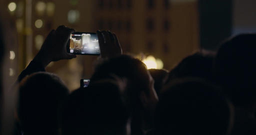 View from behind of hands hold smartphone among people at rave party with light Footage