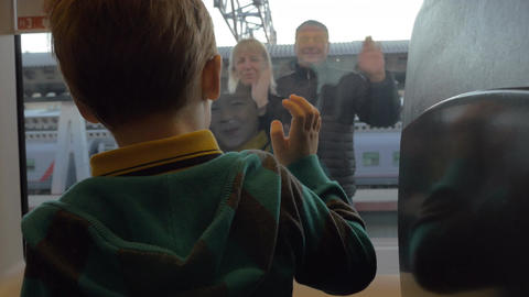 Back view of boy watching in window from rail train and saying goodbye his grand Footage