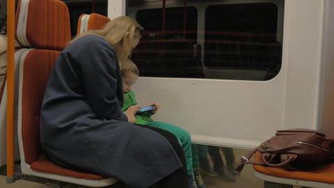Mother and child using cell in moving subway train 画像