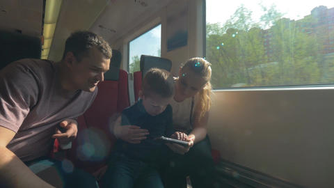 Parents and child traveling by train and using cellphone Footage