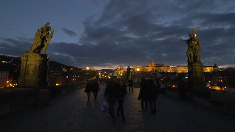 Tourists walk across Charles bridge in the evening in Prague Footage