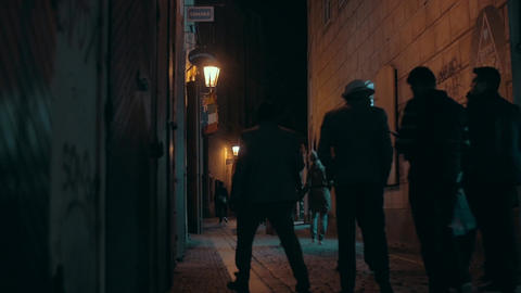 Evening cityscape with walking people silhouettes going along small paving road, Footage