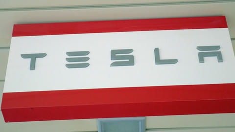 Tesla banner in the store. Automaker of electric cars Live Action