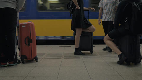 People with baggage waiting for the train at railway station Footage