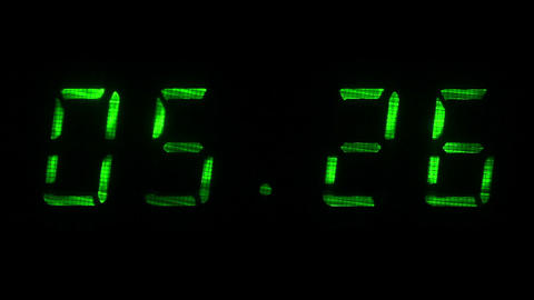 Rapid adjustment of time on the digital clock display, green digits on a black Live Action