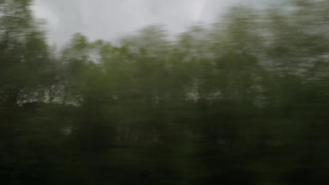 View from riding train window of coutryside landscape, trees, forests, houses ag Footage