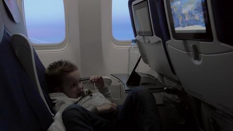 Child watching cartoon on smartphone in airplane Footage