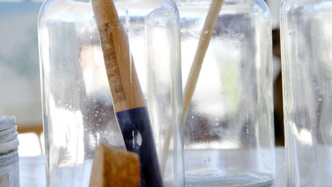 Glass jars and paint brushes Live Action