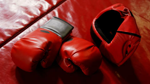Boxing gloves and headgear in boxing ring Live Action
