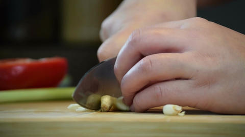 Close-up of professional chefs hand using knife to slice, chop garlic for cookin Footage