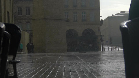 Raindrops falling on asphalt in old European city, people walking, rainy weather Footage