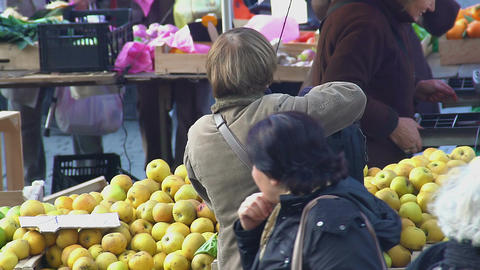 Senior woman buying apples, many people shopping at local market, eco food Footage
