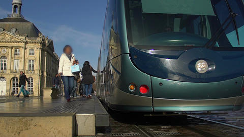 Modern blue trolley car moving to tram station, people entering transport Footage