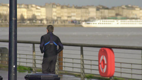 Sportive male running along river embankment in city, healthy lifestyle, fitness ビデオ