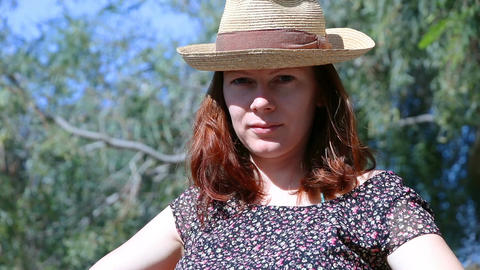 Young beautiful woman with red hairs and a straw hat sitting outside looking at Live Action
