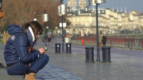 Teenage girl sitting on steps in city center and typing a message on cellphone Footage