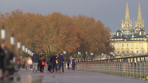 Relaxed people walking along embankment, enjoying beautiful city view, weekend Footage