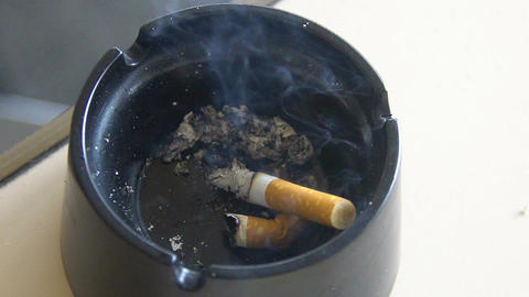 Harmful habit, smoldering cigarette butt lying in black ashtray, health problems Footage