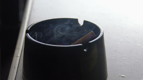 Cigarette butt smoldering in ashtray, closeup. Unhealthy lifestyle, bad habit Footage