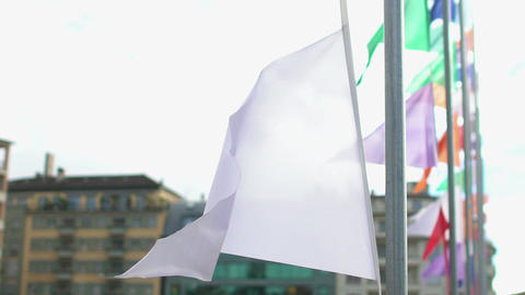 White flag waving in wind peacefully, street decorated with colorful banners Footage