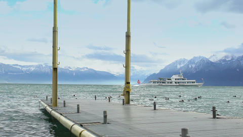 Motor cruiser with Swiss flag sailing cold stormy lake in Alps, empty mooring Footage