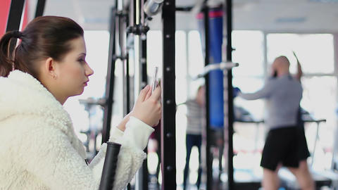 Glamorous female with smartphone taking photo of famous boxer training in gym Footage