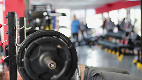 Strained man doing bench press exercise in gym, trying hard to raise barbell Live Action