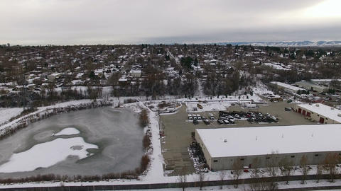 Aerial drone lift up to industrial park winter residential snow covered houses Footage
