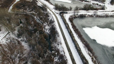 Aerial drone tilt up snowy winter running path to frozen pond and creek Footage