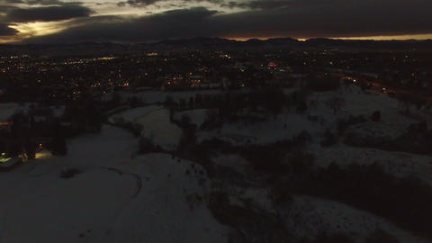 Aerial drone lift up dark late mountain sunset city lights snowy public park Footage