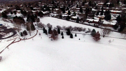 Aerial drone lift up from winter snowy park to residential housing and highway Footage